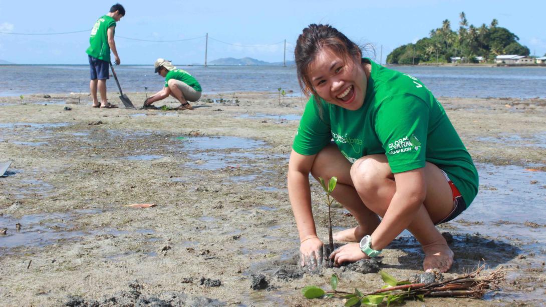 Voluntaria ambiental plantando manglares durante su trabajo voluntario en Fiyi.